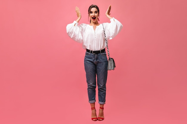 Amazed lady in stylish outfit looks into camera on pink background.  surprised woman in white wide shirt with striped handbag and red lips poses..