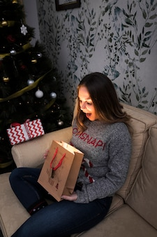 Amazed lady with gift packet on settee near Christmas tree