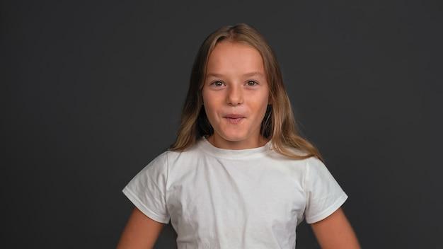 濃い灰色の壁に分離された白いtシャツを着て正面に驚いて幸せそうに立っている驚いた少女