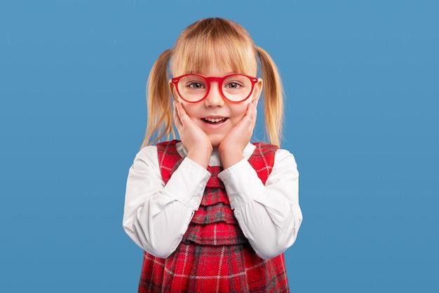 Пораженная маленькая школьница в очках