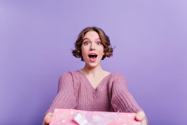 큰 분홍색 선물 상자와 함께 포즈를 취하는 곱슬 머리를 가진 놀란 사랑스러운 소녀. 선물 보라색 벽에 고립 된 세련 된 짧은 머리 젊은 아가씨.