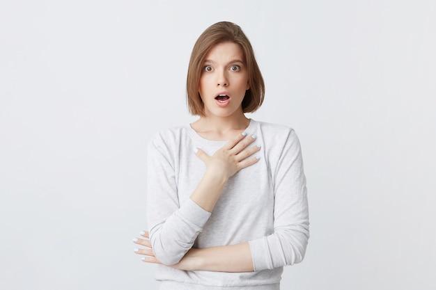 Пораженная милая молодая женщина в лонгсливе, стоя с открытым ртом и сложенными руками