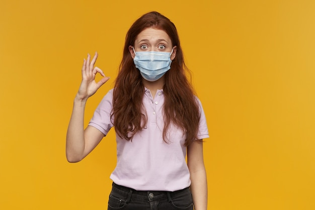 立って黄色の壁に隔離されたokサインを示している医療用保護マスクを身に着けている驚いた素敵な若い女性
