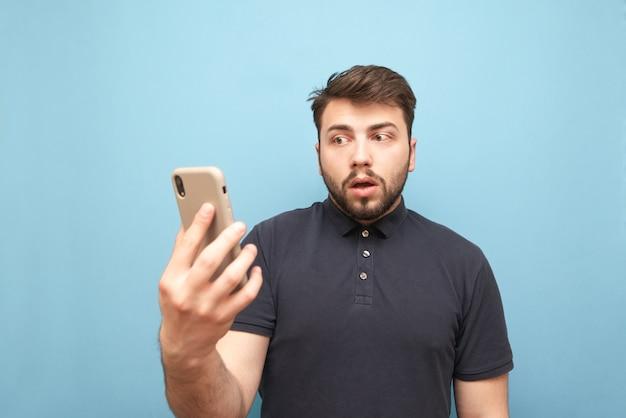 Пораженный мужчина с бородой стоит со смартфоном в руках и выглядит растерянным с растерянным лицом