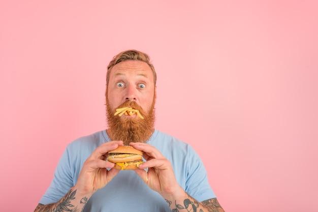 수염과 문신을 한 놀란 남자는 햄버거와 감자로 샌드위치를 먹는다