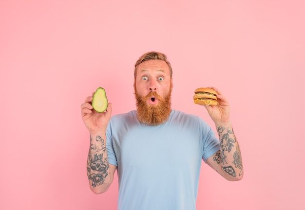 수염과 문신을 한 놀란 남자는 아보카도를 먹을지 햄버거를 먹을지 결정하지 못했다