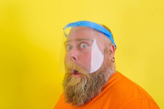 Пораженный мужчина с бородой и татуировками носит защитный щиток от коронавируса