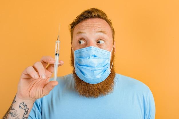 Пораженный мужчина с татуировкой бороды и маской от covid готов к вирусной вакцине