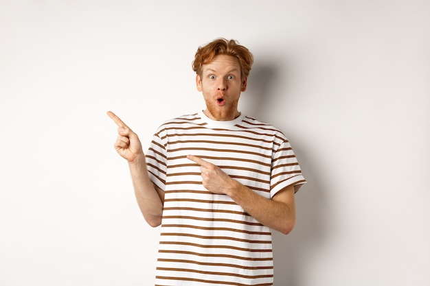 Amazed man with ginger hair checking out promo offfer, pointing left at logo and smiling at camera, standing over white background.