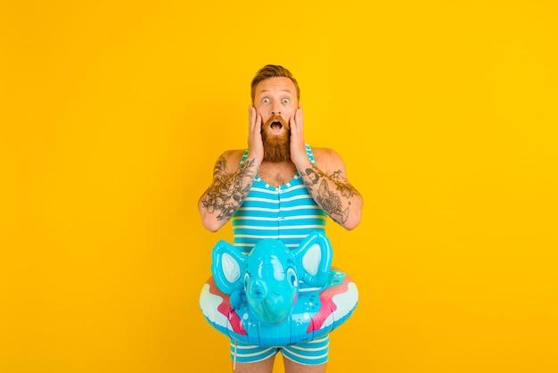 코끼리와 함께 풍선 도넛을 가진 놀란 남자가 수영할 준비가 되었습니다.