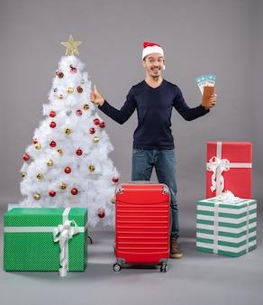 Uomo stupito con la valigia rossa ha aperto le mani con i biglietti di viaggio su grigio