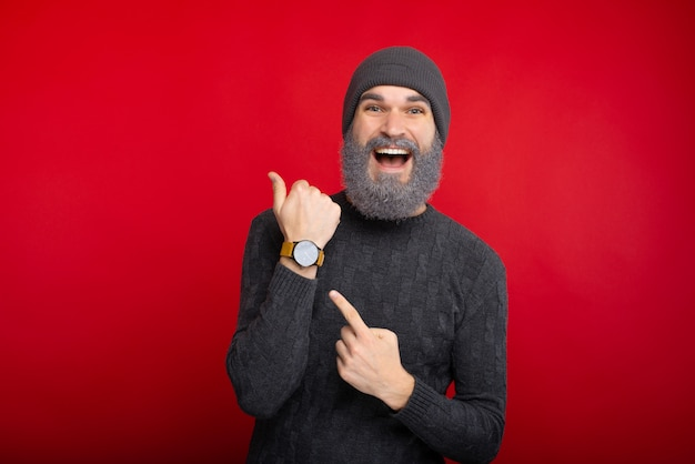 Amazed man with white beard pointing at watch