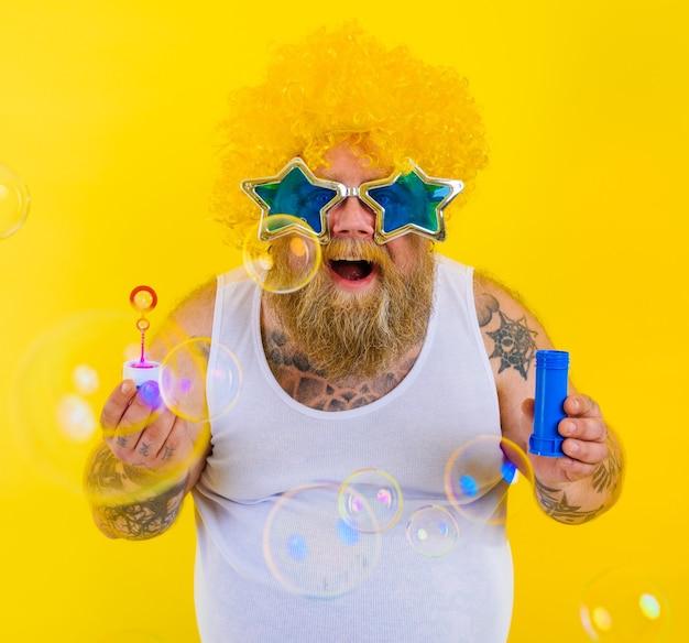 Пораженный мужчина с желтым париком в голове играет с мыльными пузырями
