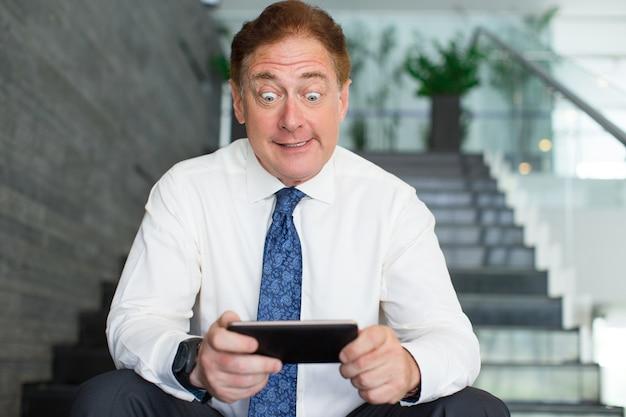 Пораженный зрелый менеджер по телефону