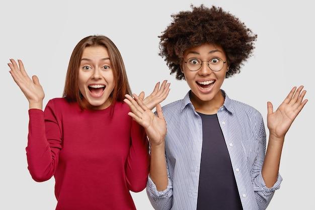 Пораженные многонациональные молодые женщины-подруги с удивлением пожимают руки, встают рядом,