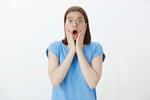 Пораженная всезнайка выглядит удивленной в очках и задыхается от удивления