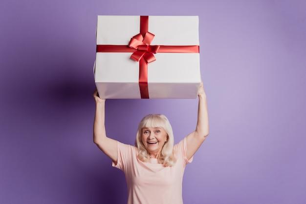 Пораженная старуха держит большую подарочную коробку, изолированную на фиолетовом фоне