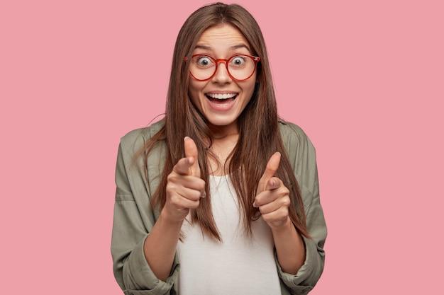 Пораженная, обрадованная европейская женщина указывает на камеру указательными пальцами, делает жест с пистолетом, приветствует друга или одобряет идею