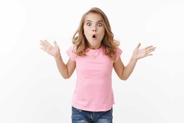 Пораженный ошеломленный молодой ребенок симпатичная блондинка объясняет родителям невероятные новости, жестикулирует, поднимает руки, полное недоверие, изумление и волнение, надувает складки губ, изумленно произносит