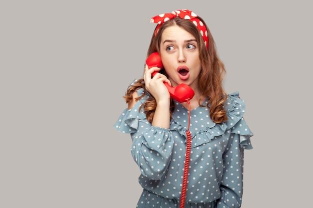 電話の携帯電話を持って驚いたピンナップガールのフリルブラウスが会話に驚いて、口を開けてショックを受けた