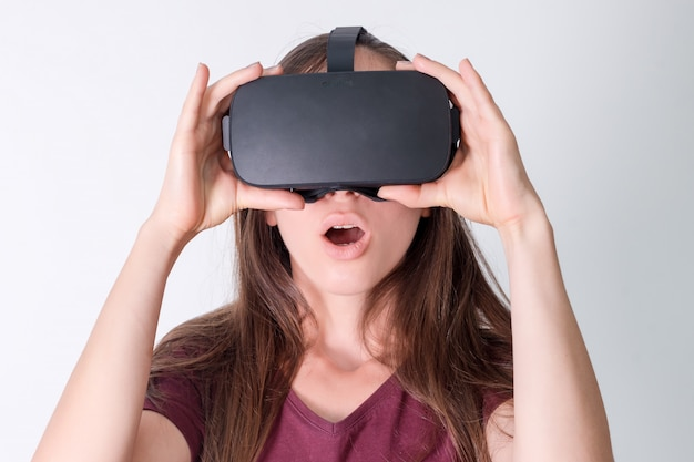 Amazed positive woman wearing virtual reality goggles headset, vr box. connection, technology, new generation, progress concept. girl surprised by something in virtual reality. studio shot on gray