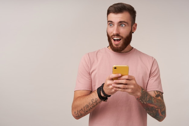 Amazed pretty bearded guy with tattooes looking aside with wide eyes and mouth opened, keeping his mobile phone in hands while posing on white in casual clothes