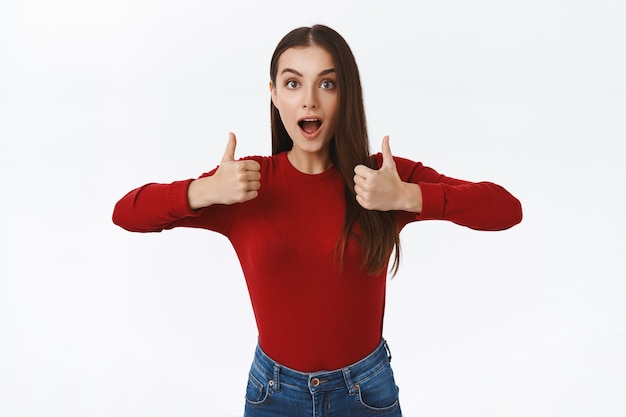 Amazed pretty caucasian brunette girl obsessed with awesome idea. showing thumbs-up, gasping and open mouth fascinated, agree or like stunning thing, standing white background