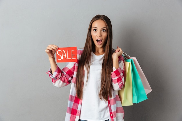 Amazed pretty caucasian woman holding sale sign and shopping bags
