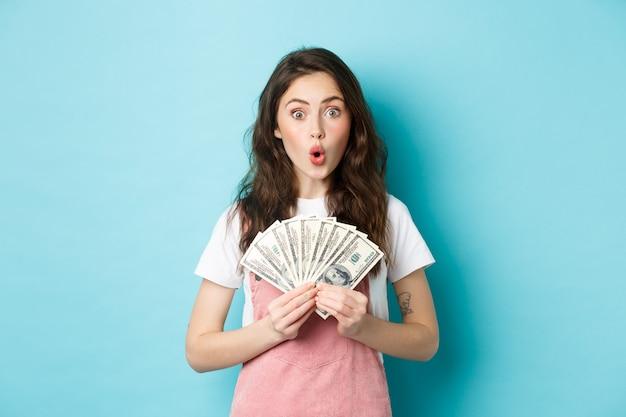 Amazed pretty female model holding dollar bills, winning money, got credit for shopping, standing amazed against blue background.