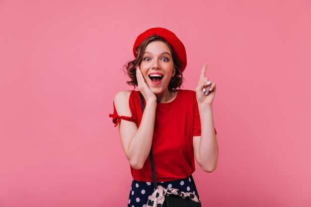 Bella ragazza stupita con il tatuaggio che esprime emozioni positive. raffinata signora francese in berretto e maglietta rossa.