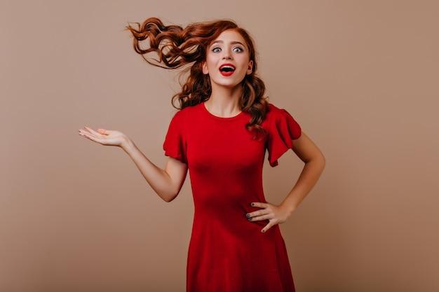 장난스럽게 포즈를 취하는 놀란 예쁜 여자. 진정한 감정을 epxressing 빨간 드레스에 긍정적 인 백인 소녀.