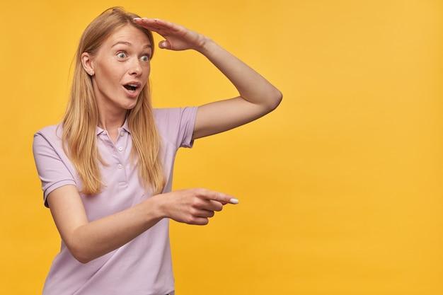 Пораженная симпатичная женщина с веснушками в бледно-лиловой футболке, указывающая в сторону на copyspace и смотрящая вдаль на желтый