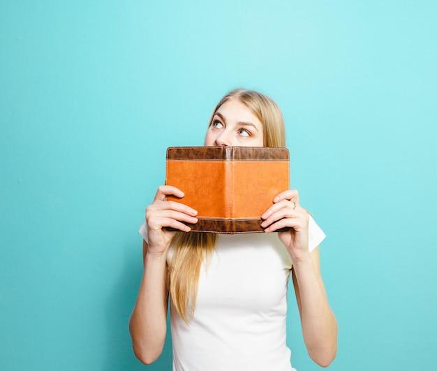 黄色の背景の上の本で顔を覆っているかなり若い女性を驚かせた