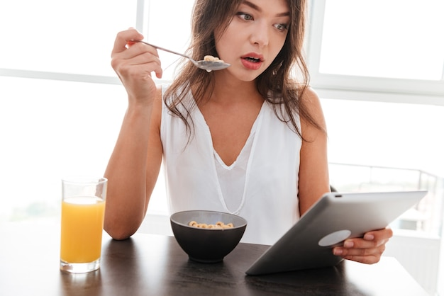 Amazed pretty young woman having breakfast and using tablet on the kitchen