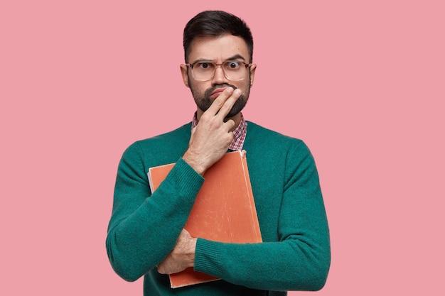 Ragazzo europeo stupito perplesso con setole spesse, labbra increspate, vestito con un maglione verde, grandi occhiali quadrati, tiene in mano un vecchio libro di testo rosso