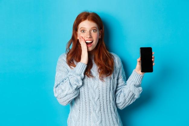 카메라를보고, 스마트 폰 화면을 보여주는, 모바일 응용 프로그램을 시연, 파란색 배경 위에 서 놀된 빨간 머리 소녀.