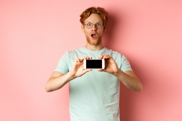 Amazed redhead man gasping and staring with awe at camera, showing blank smartphone screen horizontally, standing over pink background.