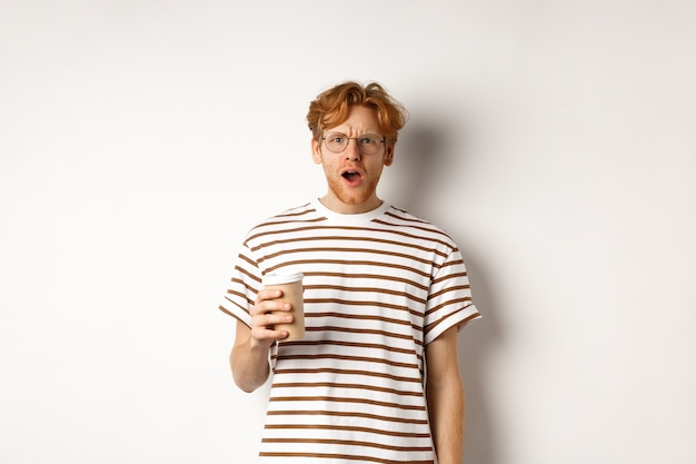 Amazed redhead man in glasses holding coffee cup and staring at camera with complete disbelief, standing in striped t-shirt against white background.