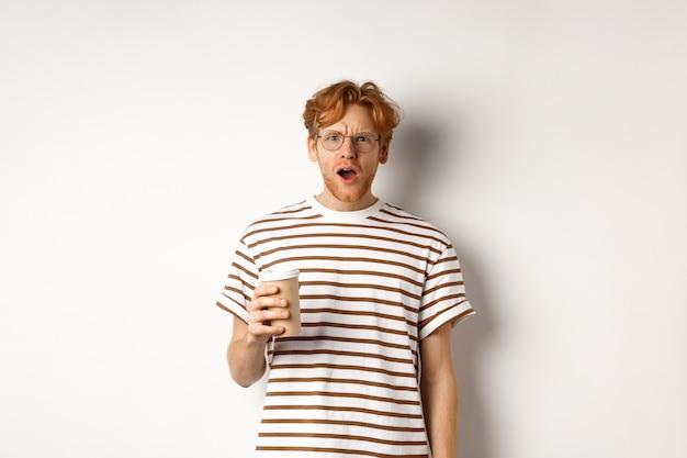 Пораженный рыжий мужчина в очках держит чашку кофе и с полным недоверием смотрит в камеру, стоя в полосатой футболке на белом фоне.
