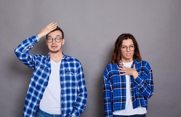 Пораженные грустные женщина и мужчина пожимают плечами, понятия не имеют, одеты в повседневную одежду
