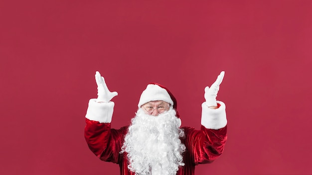 Amazed santa claus in hat with hands up