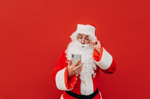 Amazed santa claus is touching his goggles and feeling surprised