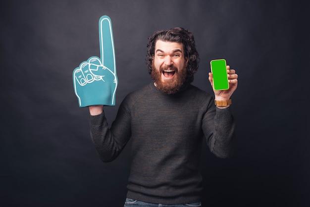 Пораженный кричащий молодой бородатый мужчина с фанатской перчаткой показывает зеленый экран на телефоне