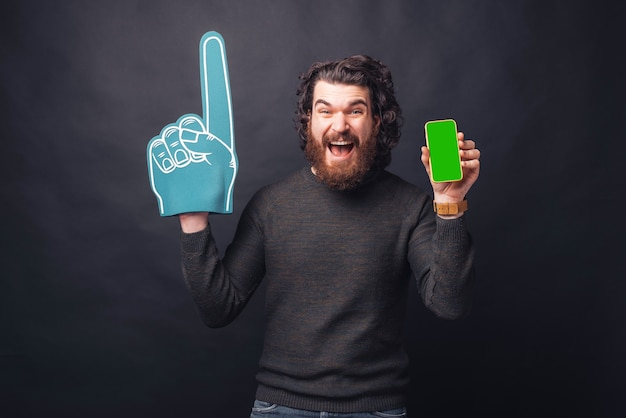 Amazed screaming young bearded man with fan glove showing green screen on phone