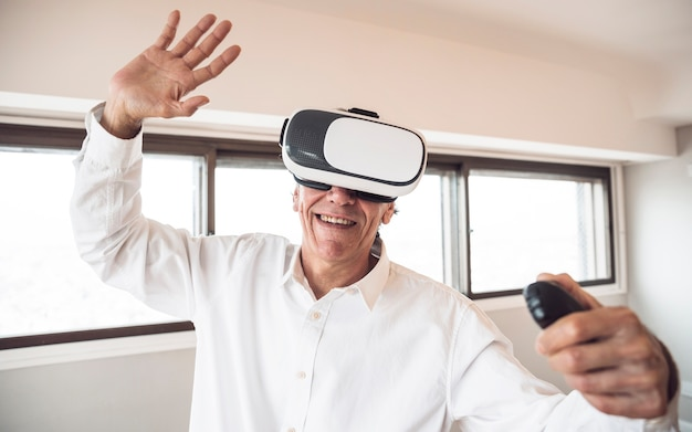Amazed senior man touching in the air during the vr experience