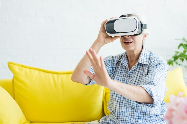 Amazed senior woman touching the air during the vr experience