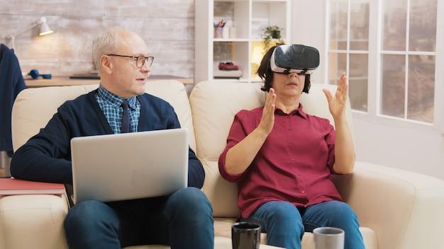 Пораженная старшая женщина, использующая очки виртуальной реальности на диване, с мужем рядом с ней, использующим ноутбук.