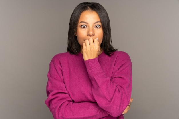 충격을 받은 아프리카계 미국인 여성이 충격을 받은 눈을 크게 뜨고 뉴스에 당황하거나 놀랐습니다.