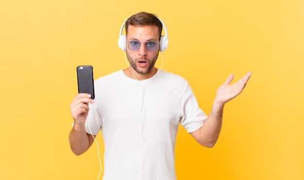ヘッドフォンとスマートフォンで音楽を聴きながら、信じられないほどの驚きに驚き、ショックを受け、驚きました