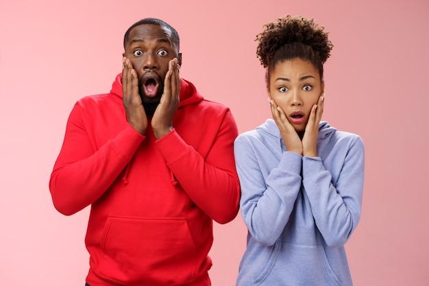 驚いたショックを受けたあえぎ言葉のない2人のアフリカ系アメリカ人男性女性ドロップジョープレス手のひら頬心配神経質な共感恐ろしい話立って唖然としたピンクの背景、ごめんなさい